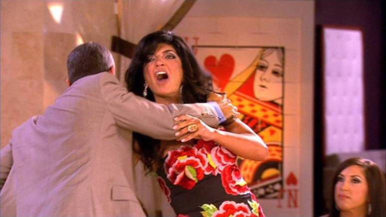 Andy Cohen holds Teresa Giudice back as she tries to attack Danielle Staub.
