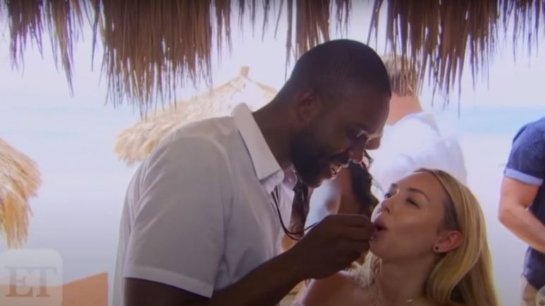 DeMario Jackson puts something in Corinne Olympios' mouth on the set of Bachelor in Paradsie