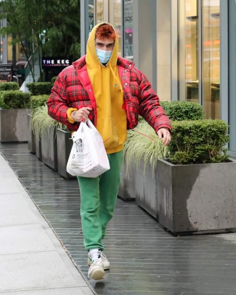 Image of KJ Apa carrying a grocery bag.