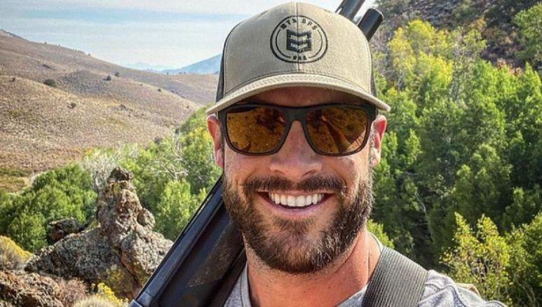 Garrett Yrigoyen with a a gun in nature