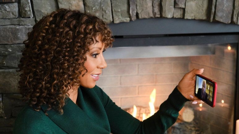 Holly Robinson Peete standing by a fireplace