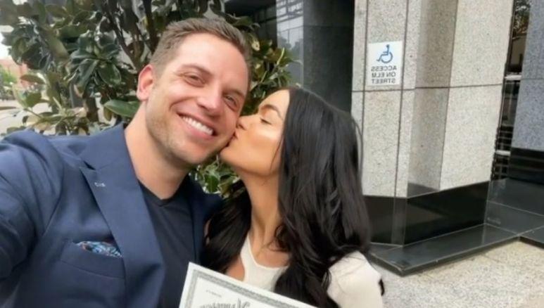 Raven Gates and Adam Gottschalk hold their marriage certificate