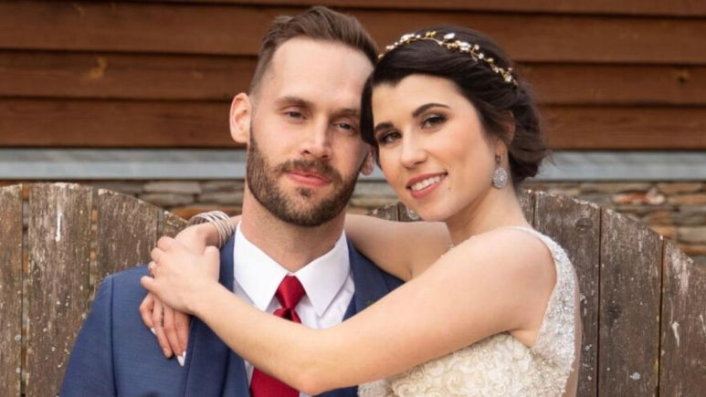 Matt holds Amber while they wear their wedding attire