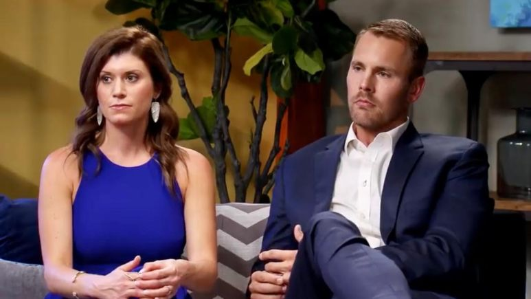 Dave and Amber wear formal attire while sitting on the couch