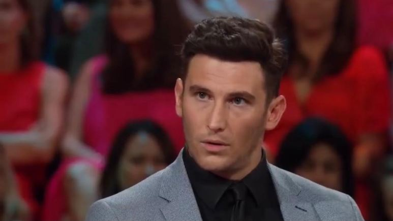 Blake Horstmann gives an intense look to the left while wearing a suit