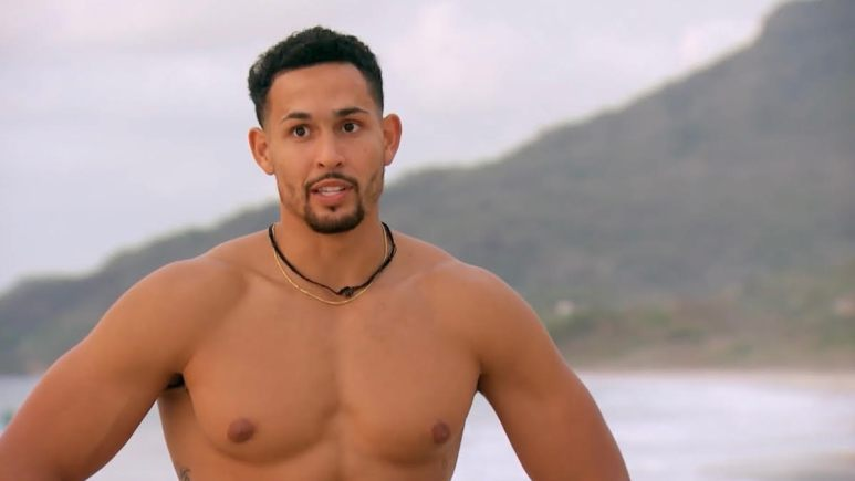 Thomas Jacobs stands shirtless on the beach