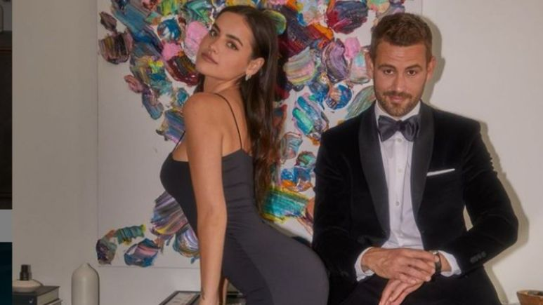 Natalie Joy in a black dress sticking her butt out with boyfriend Nick Viall standing next to her in a black suit with a bowtie and Converse sneakers