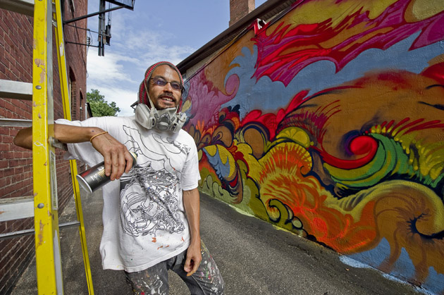 Mike Ming rests at his mural, in progress, at Personal FX Hair Salon