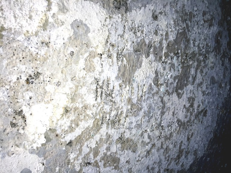 """Prisoners once counted the days in """"The Hole"""" beneath the old Montana State Prison by carving marks in the whitewashed plastered walls. - John S. Adams photo"""