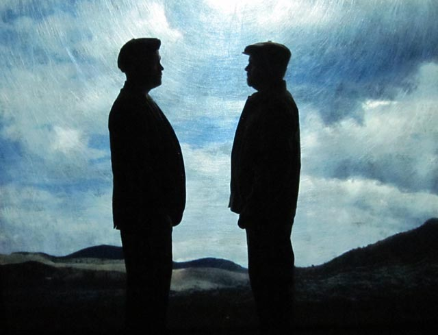 (J. McAndrew Breen) and (Kevin Dykstra) in silhouette in front of projected scenery