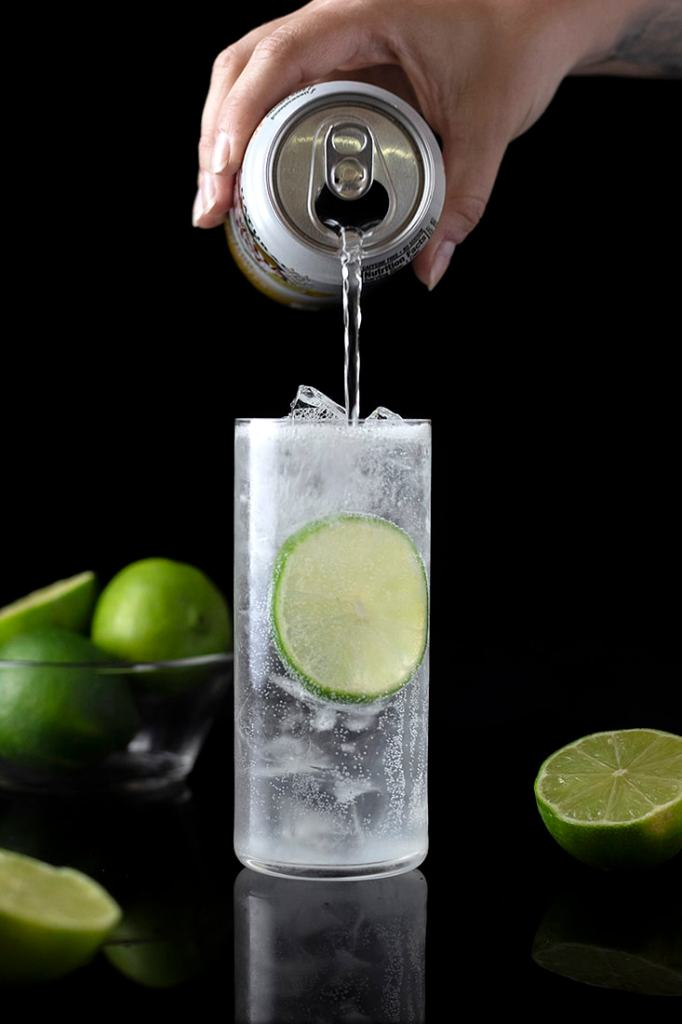 pouring seltzer into highball glass with gin and lime juice