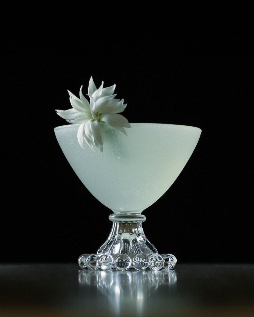a white cocktail in a coupe glass with a white flower garnish.