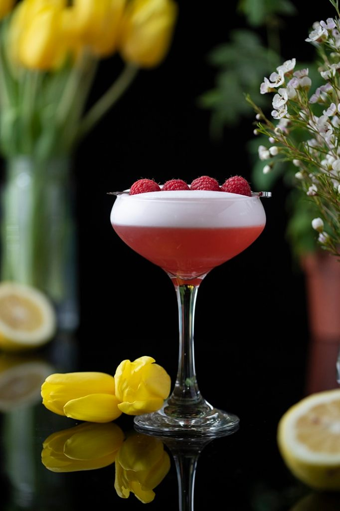 red cocktail in a coupe glass with yellow tulips