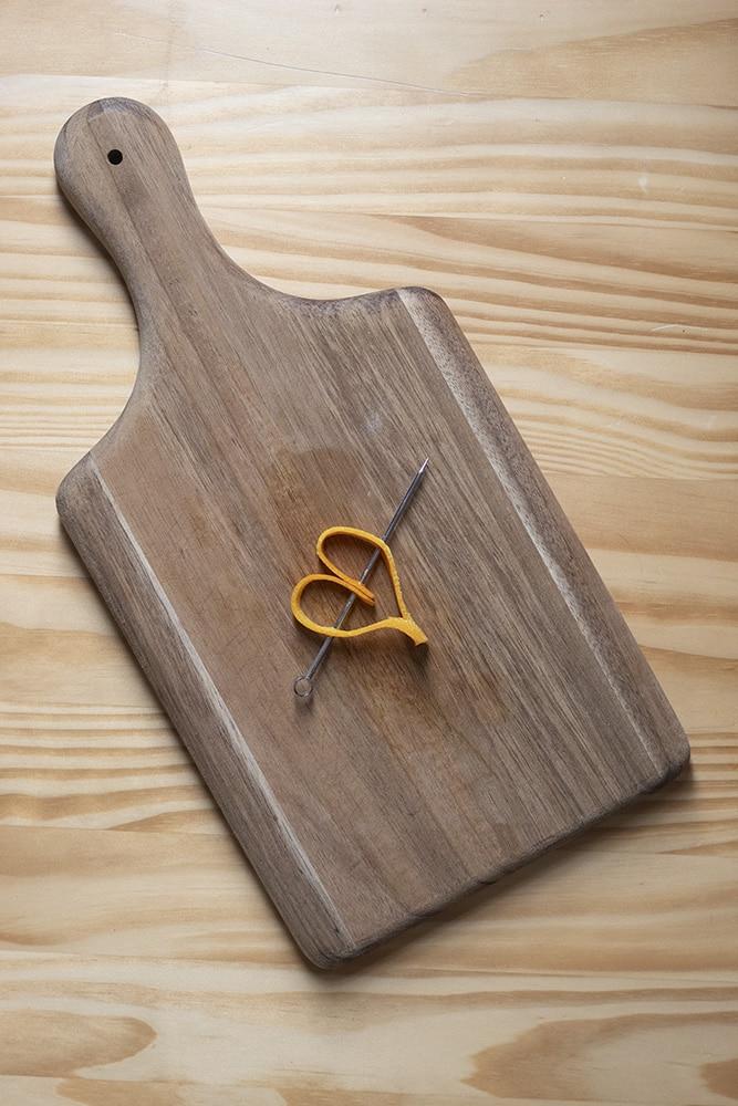 an orange peel shaped into a heart on a cocktai pick