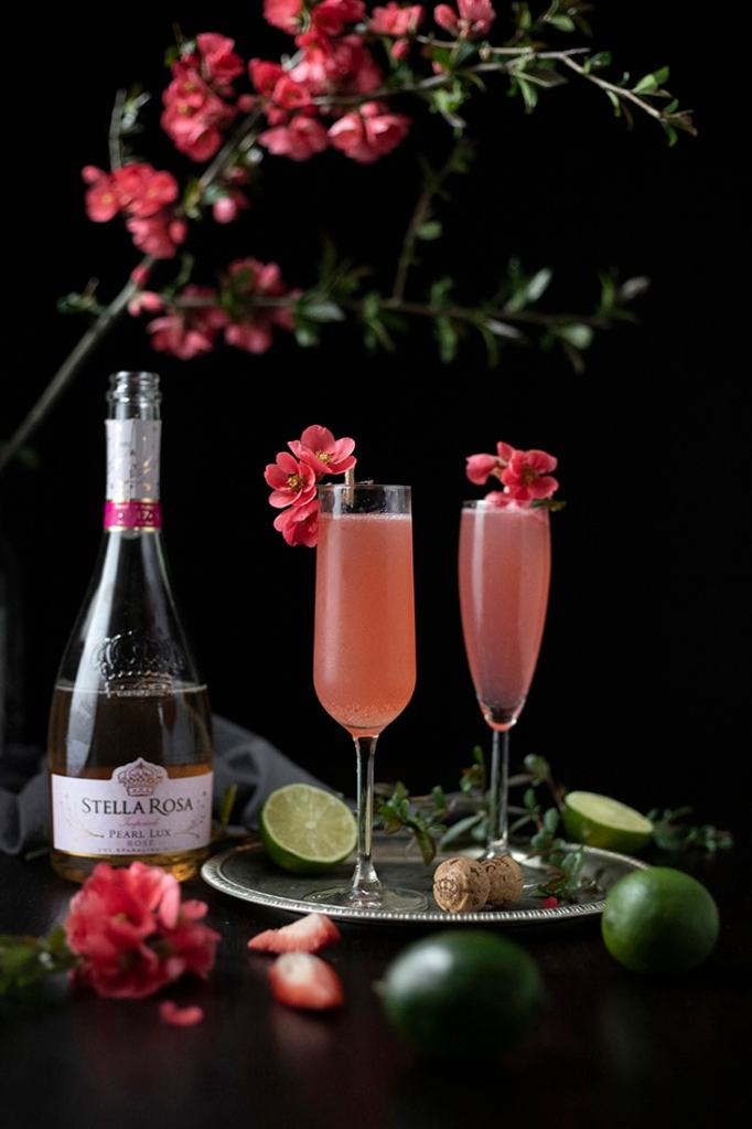 two pink cocktails in champagne flutes on a silver tray next to a bottle of opened Stella Rosa Pearl Lux Rose