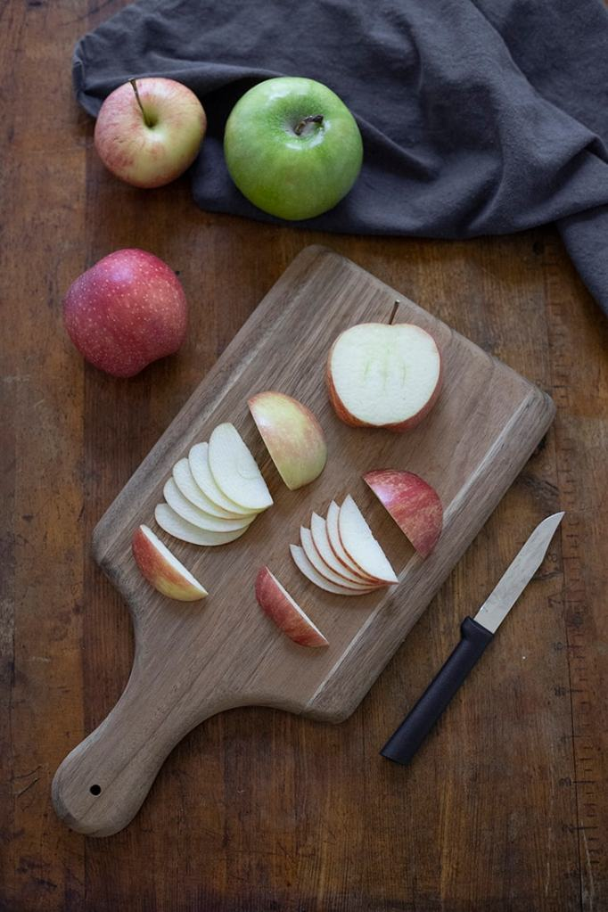 red apples sliced into pieces for apple fans on a cutting board surrounded by apples and a knife