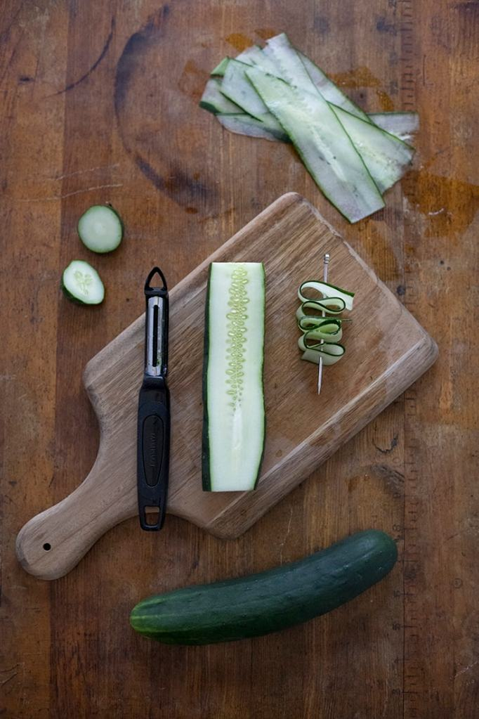 cucumbers, a vegetable peeler, and a cocktail pick with cucumber ribbons skewered onto it.