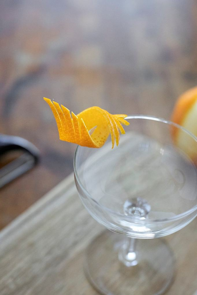 a fancy cut orange twist on the edge of a coupe glass
