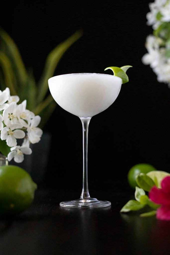 a frozen white cocktail in a long stemmed coupe glass on a black background with limes