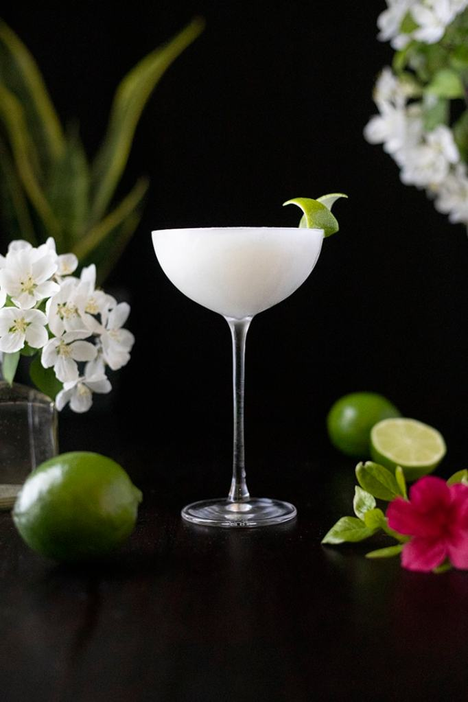 frozen white cocktail in a coupe glass on black background with limes and white flowers