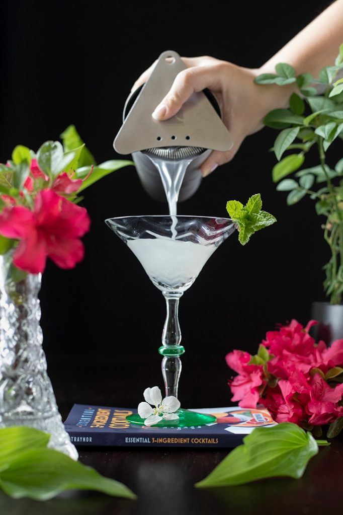 pouring a shaken cocktail from the shaker into a martini glass on a black background with red flowers