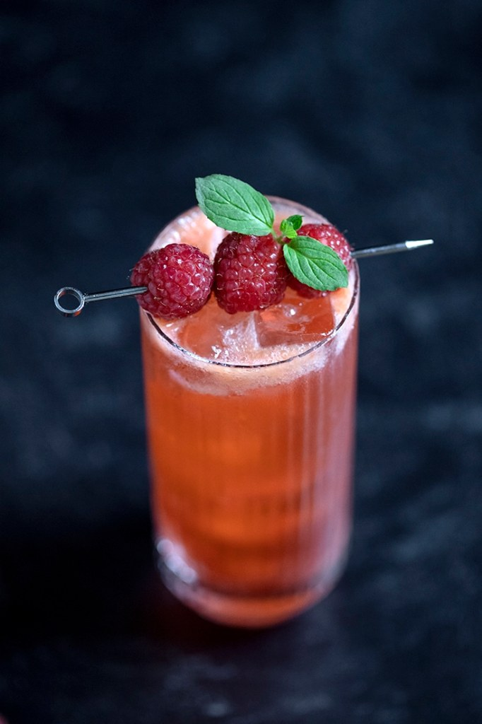 top down view of a tall red cocktail garnished with raspberries and mint leaves