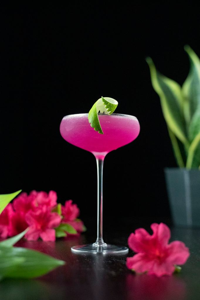 neon pink cocktail in a tall coupe glass garnished with a lime twist