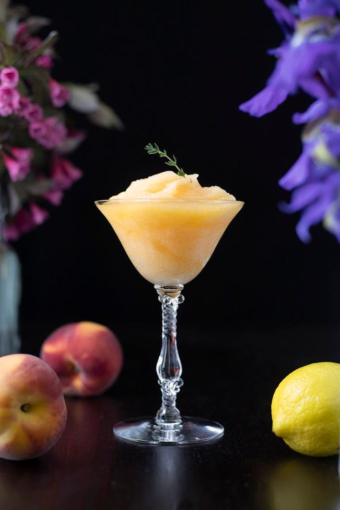 frozen yellow cocktail in a coupe glass garnished with thyme