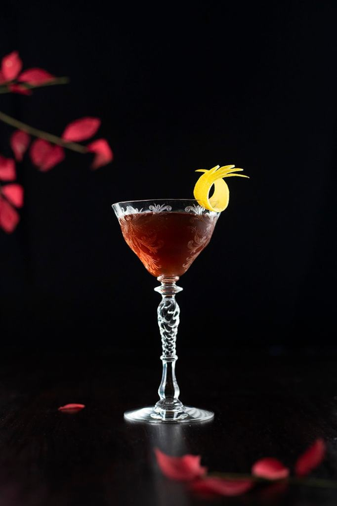 brown cocktail next to red leaves