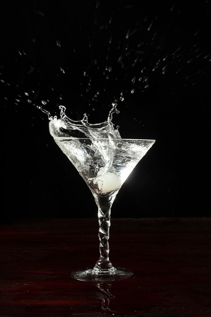 a cocktail onion splashing into a martini