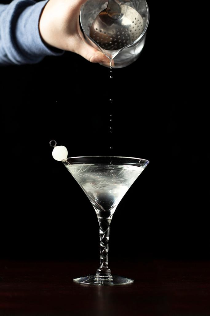 a few drops pouring from a cocktail mixing glass into a martini glass