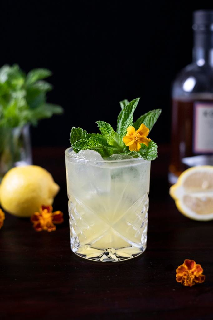 pale yellow cocktail in a rocks glass with mint and flowers