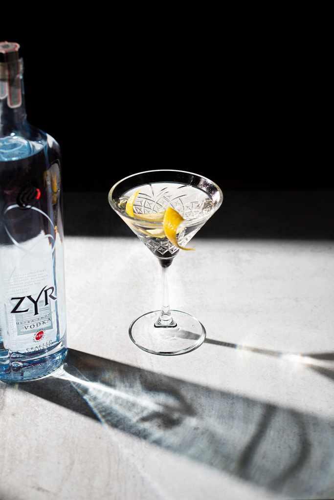 a martini with lemon twist next to a Zyr vodka bottle.