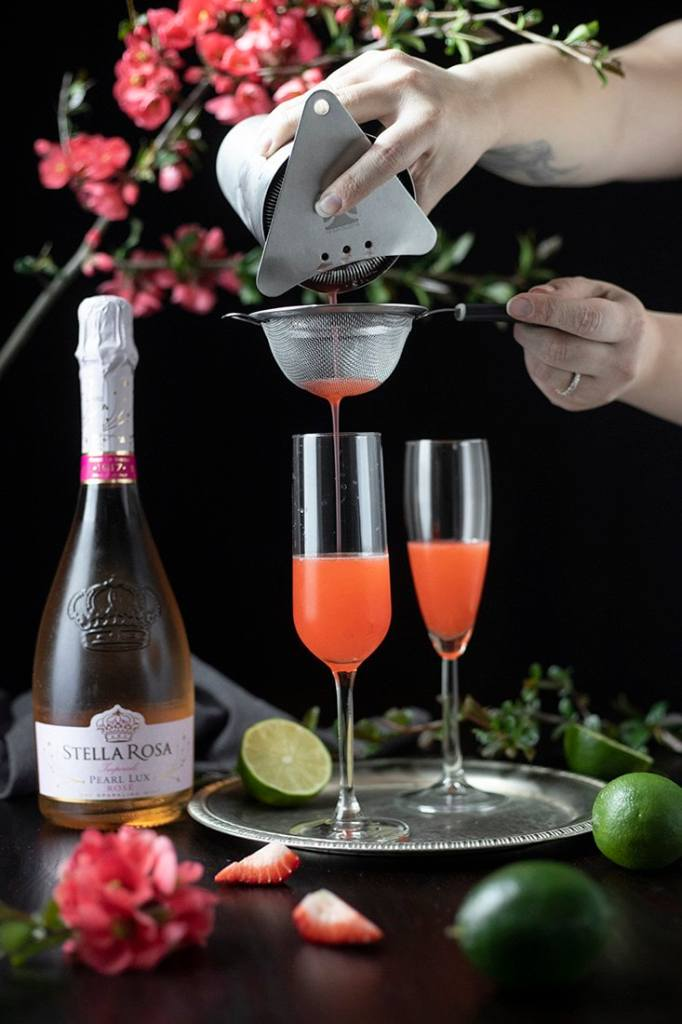 straining the cocktail into champagne flutes