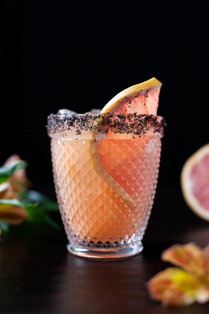 pink cocktail in a double rocks glass with grapefruit wheel