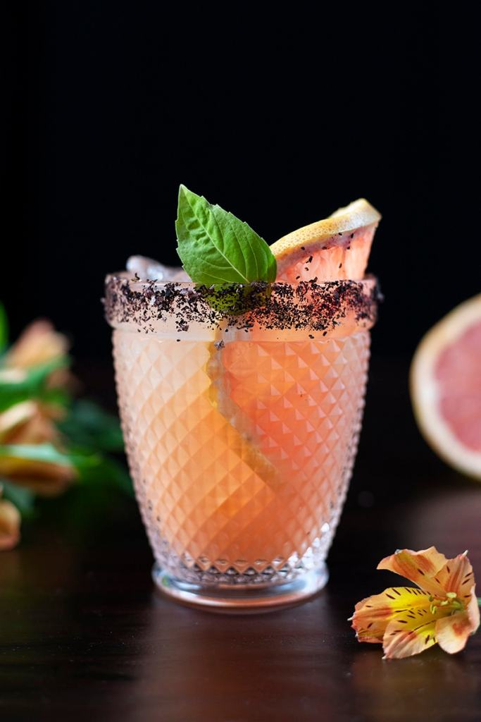 pink cocktail in a double rocks glass with grapefruit and a basil leaf