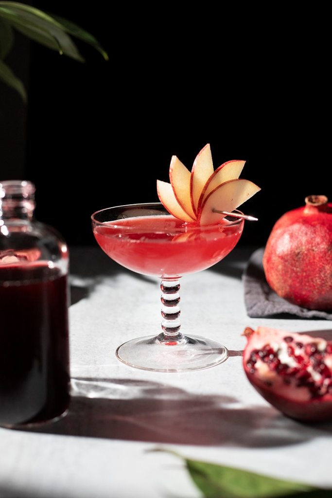 red cocktail next to pomegranate