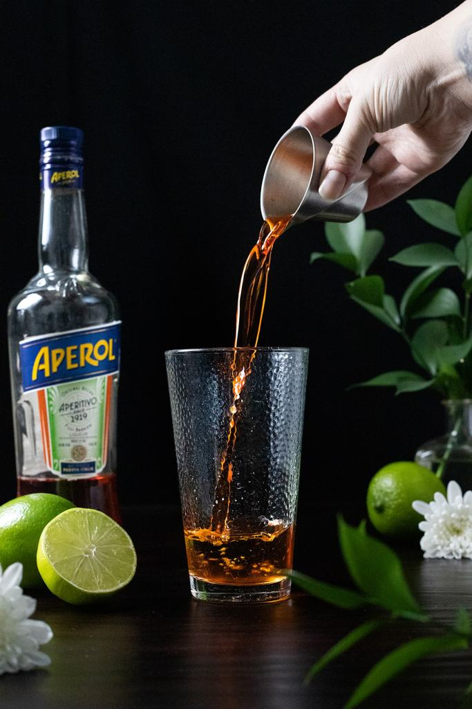 pouring an ounce of Aperol into a mixing glass.