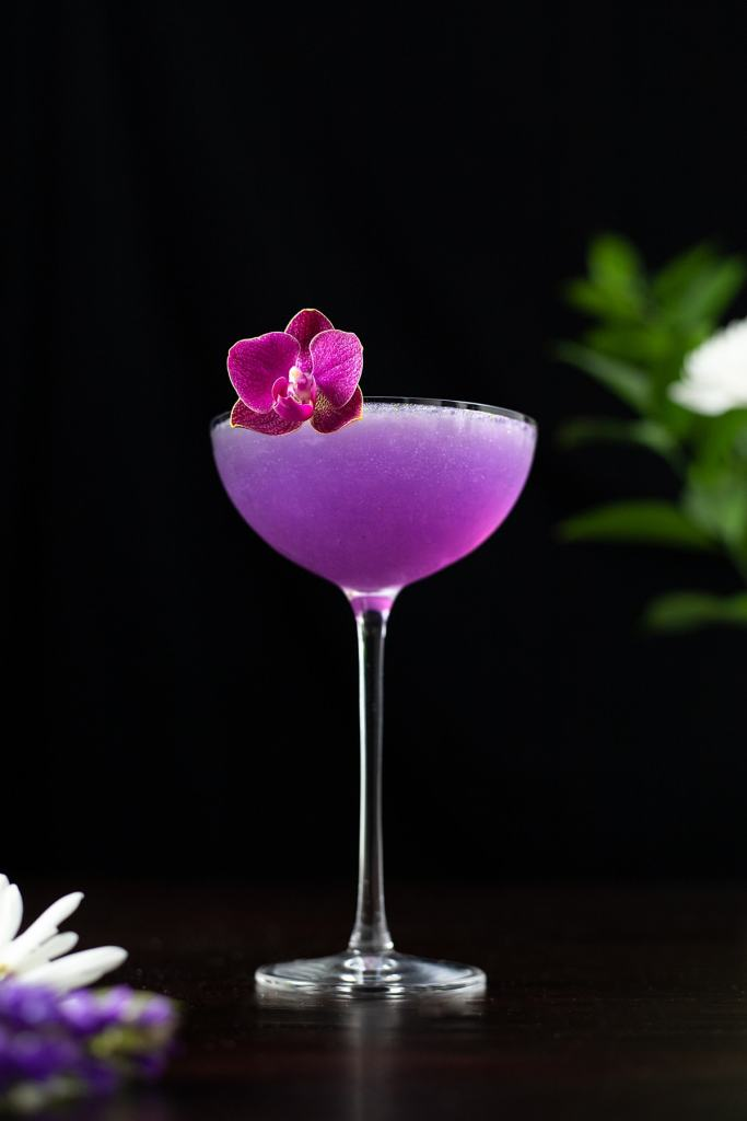 purple violet and peach cocktail in a coupe glass.