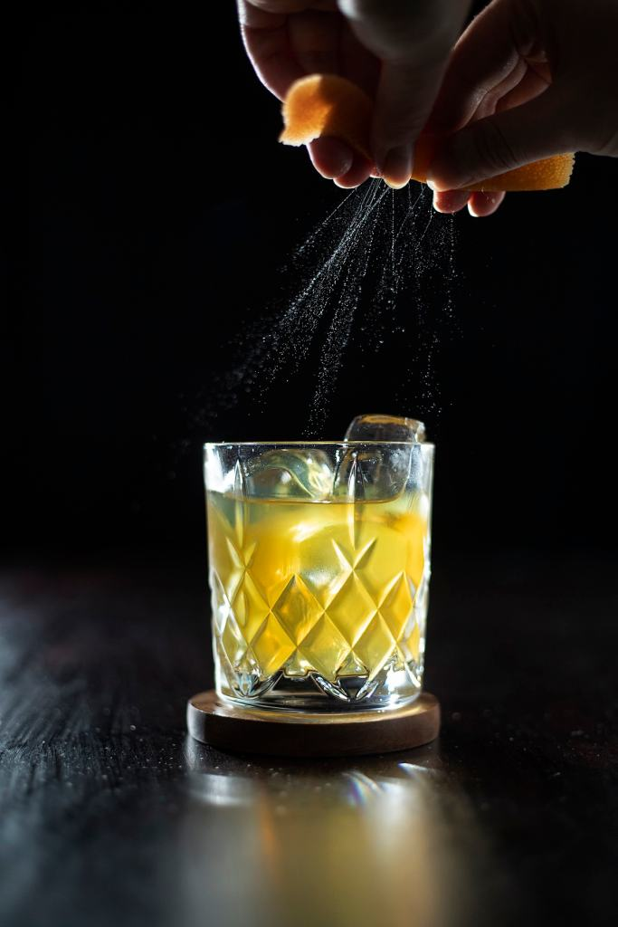 oils from an orange peel spraying onto a cocktail.