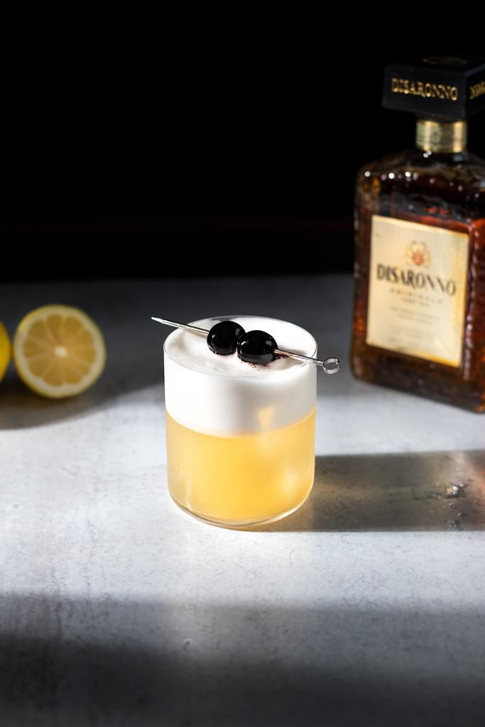amaretto sour cocktail with a bottle of Disaronno.