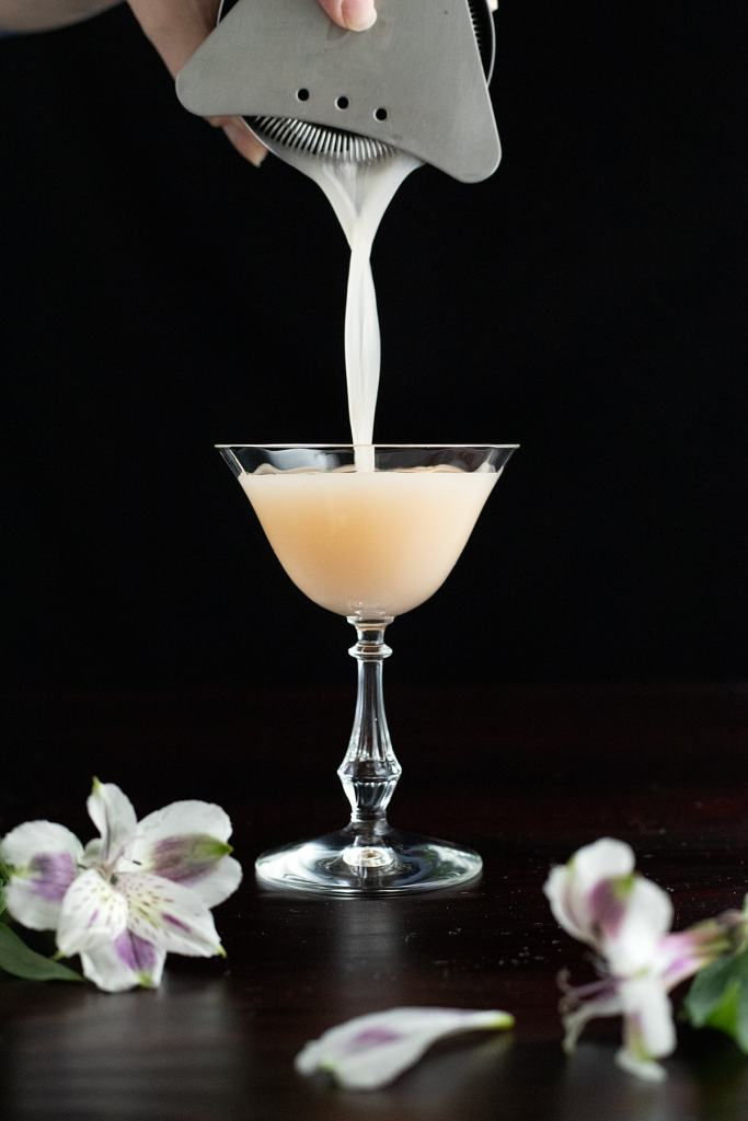 pouring an Army and Navy cocktail into a coupe.