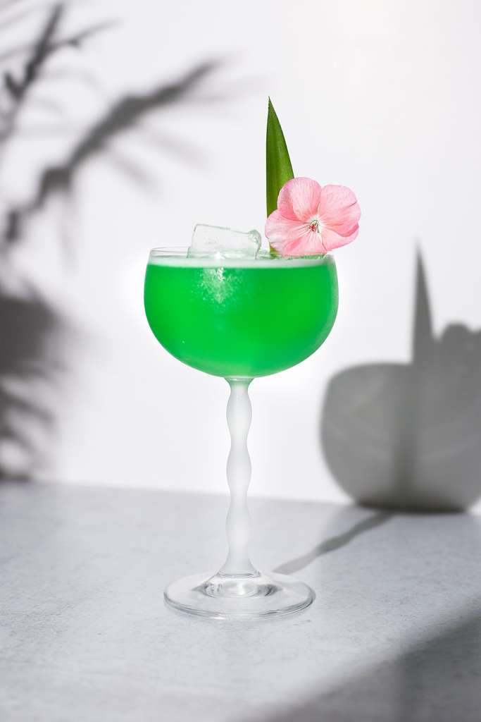 a neon green drink in a tall coupe glass.
