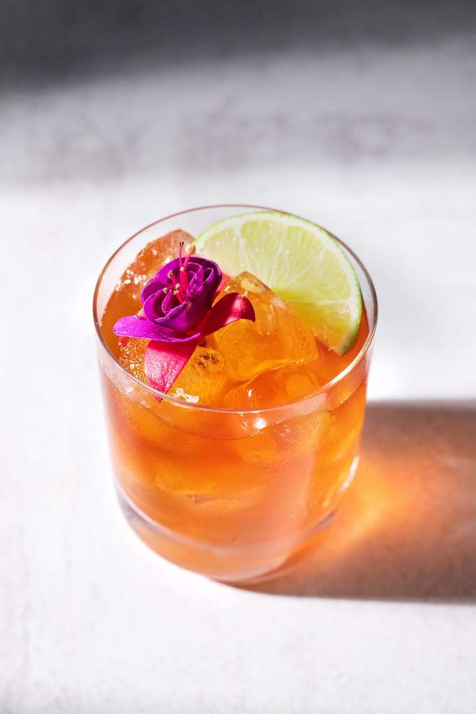 a brown cocktail in a rocks glass with a flower and lime wedge.