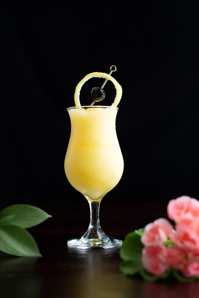 frozen yellow cocktail garnished with a circle of lemon peel and cherry.