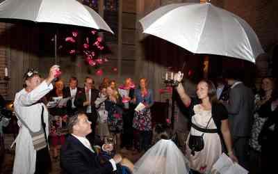 Rozenblaadjes vallen uit de opengeklapte paraplu's