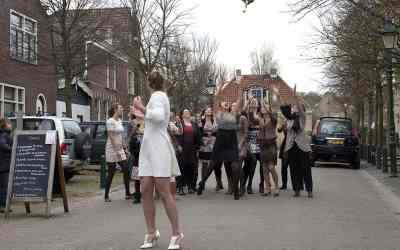 De bruid gooit het bruidsboeket hoog in de lucht & de vriendinnen staan klaar