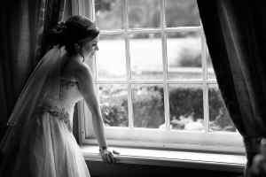 zwart-wit trouwfoto bruid bij raam