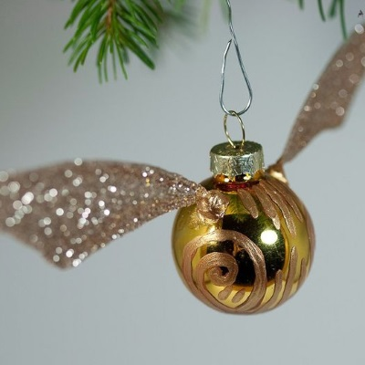 our christmas decoration ideas for book lovers include a tutorial on how to turn a christmas bauble into the golden snitch perfect for harry potter fans