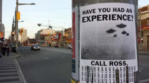 Photo of a poster on a hydro pole asking 'have you had an experience' and showing UFOs